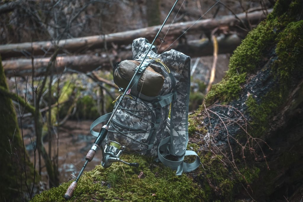 Fishing backpack and rod in forest