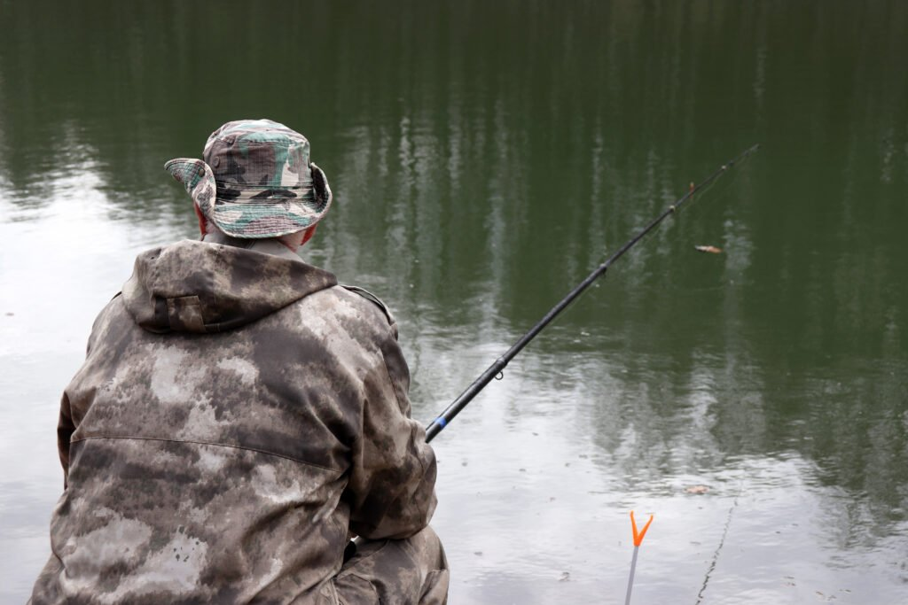 Fisherman in camouflage clothes sitting with a fishing rod on the shore. Man angling on the lake in spring, trees are reflected in the water