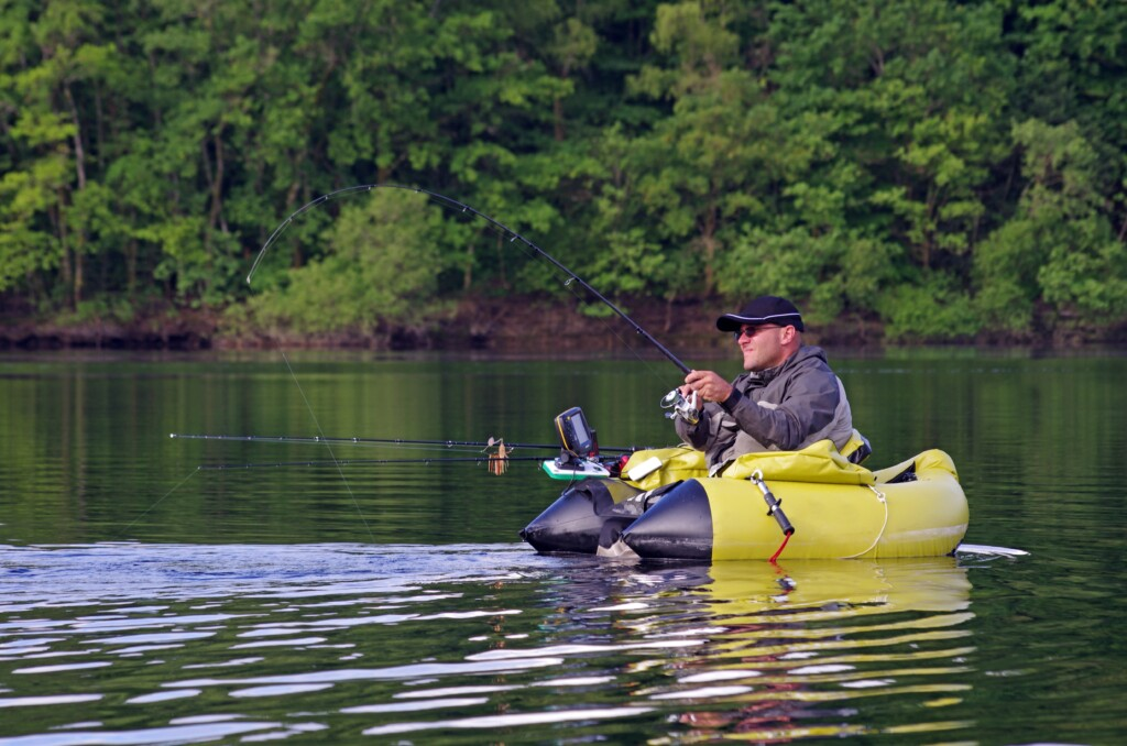 A fisherman fight against a pike. The man is sitting in the fishing inflatable boat and he use flippers to move on the water.