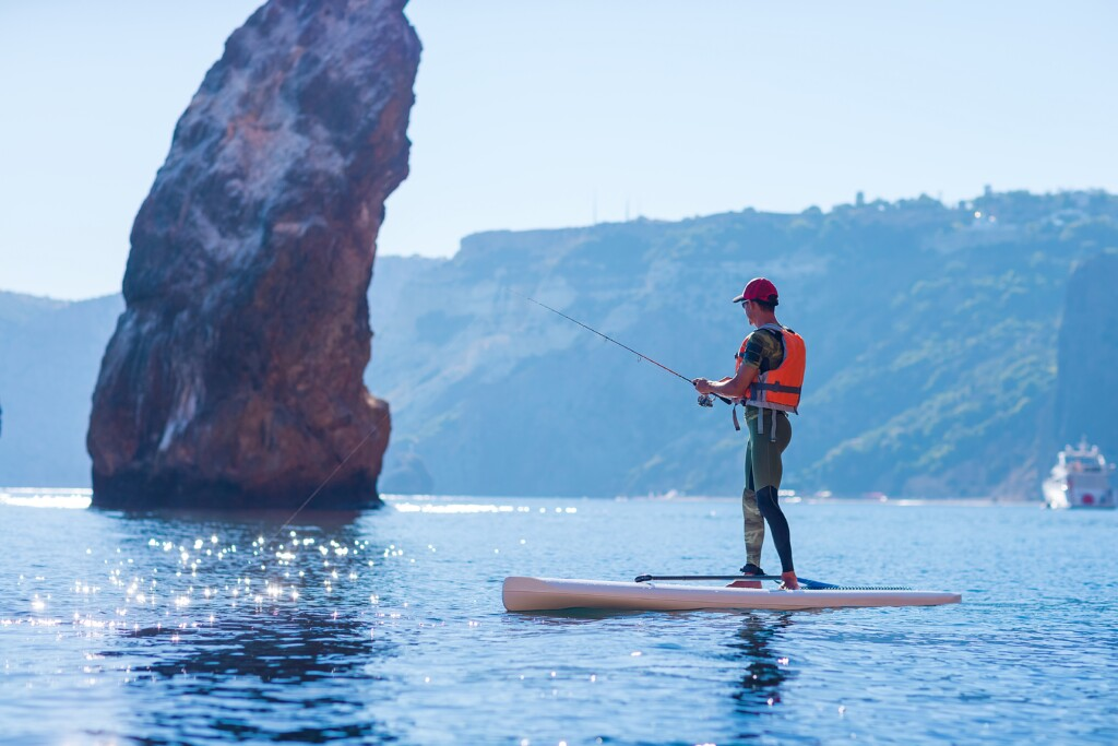 A man fishes on a fishing tackle in the standup paddleboard