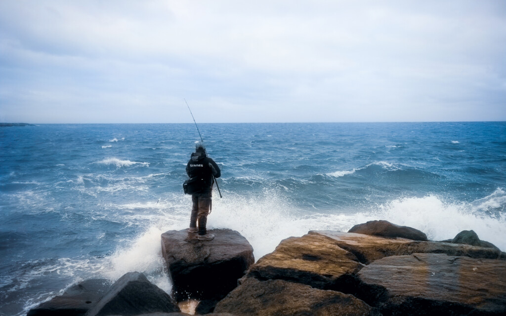 man fishing in stormy water