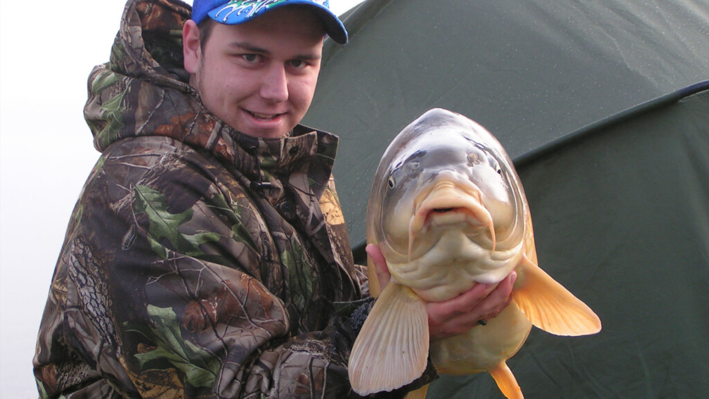 angler with a large carp he caught fishing